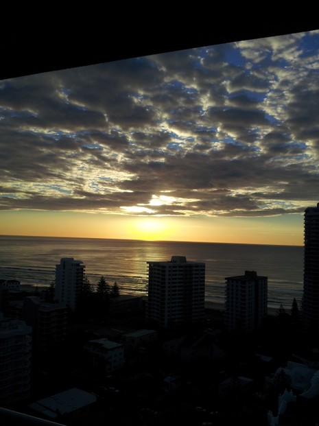 Sun Breaks Through Dark Clouds at Sunrise at Surfers Paradise