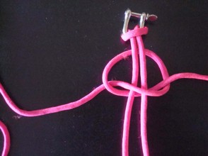 Bring the left hand cord over the right hand cord and tuck it under the stationary cords,through the hole left by the