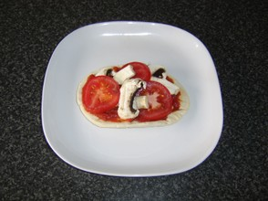 Tomato and mushroom slices are laid atop the tomato sauce