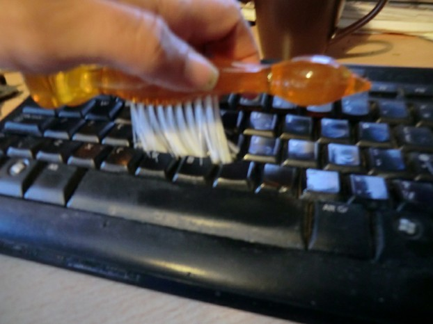 Image:  Cleaning a keyboard with a brush.