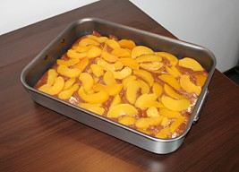 Pour the mix into a baking tray and top with the peach slices