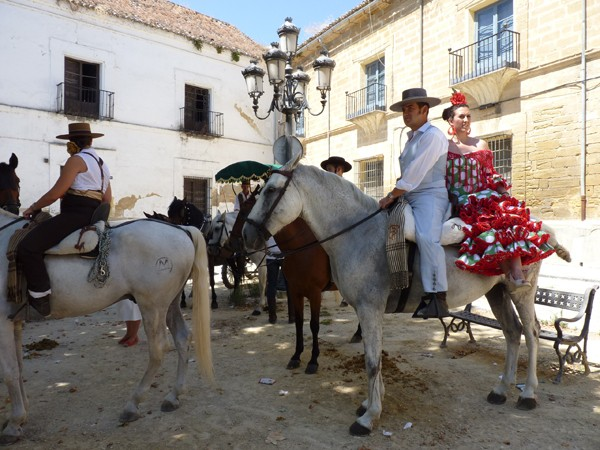 Girl in flamenco dress on horseback during local fiesta in Andalusia