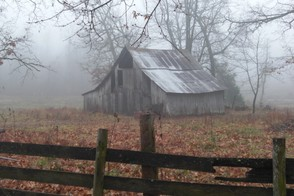 An old barn surrounded by fog