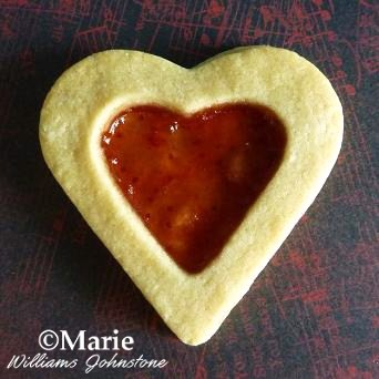 Add strawberry jelly jam preserve to the middle of heart cookies for a delicious sweet treat