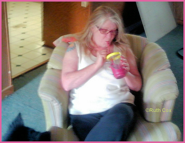 Ruthi sips a smoothie with a glass straw.