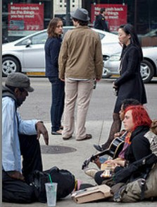 Young Lady Looking At People Sitting On Sidewalk