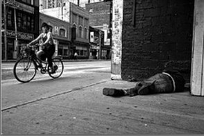 Girl On Bicycle Looks At Man Sleeping In Alley