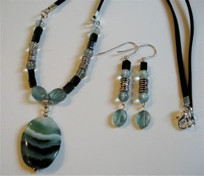 Light blue-green fluorite mixed with banded onyx, suede and metal findings.