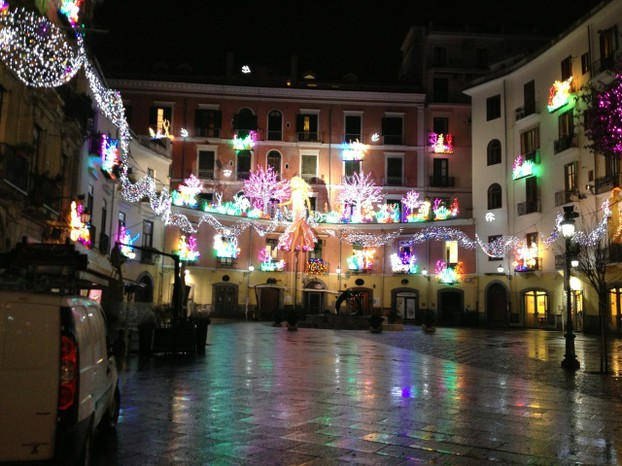 On a rainy January night, the lights reflect a colorful rainbow on a Salerno piazza.
