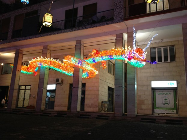 A colorful Chinese dragon weaves his way around a building front in Salerno.