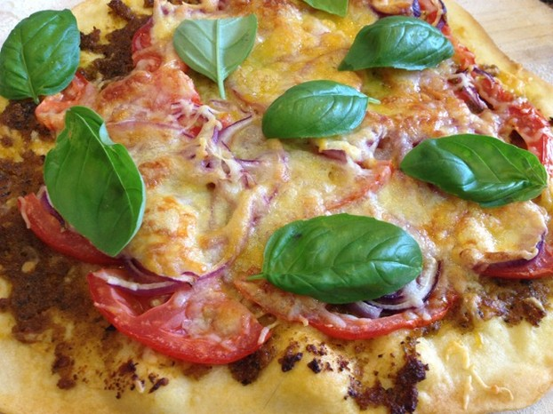 Homemade pizza with red pepper pesto and fresh tomatoes