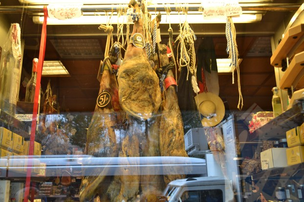 Prosciutto hams hanging in a deli window in Rome, Italy
