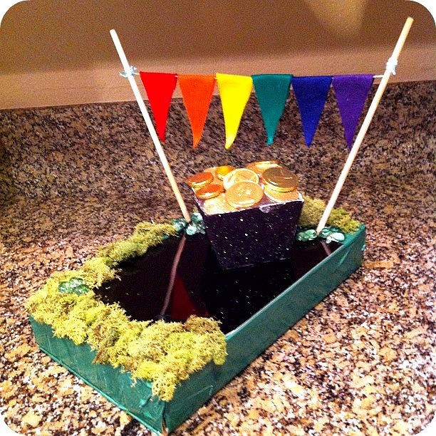 Homemade leprechaun trap with gold coins and a rainbow colored banner