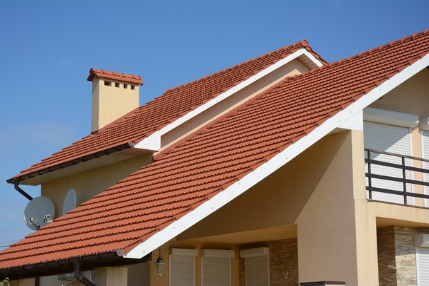 House with clay tile roof, rain gutter, chimney, gable and valley type of roof construction
